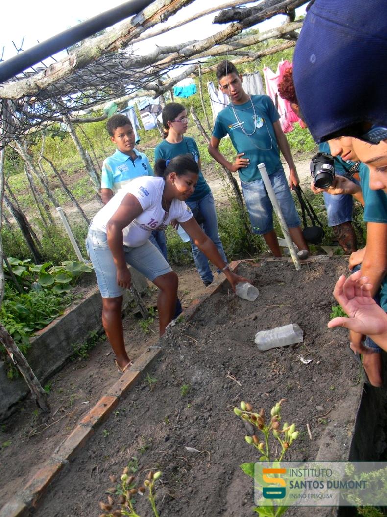 Jucicleide demonstra aos alunos o funcionamento do sistema de irrigação que a comunidade para a horta.